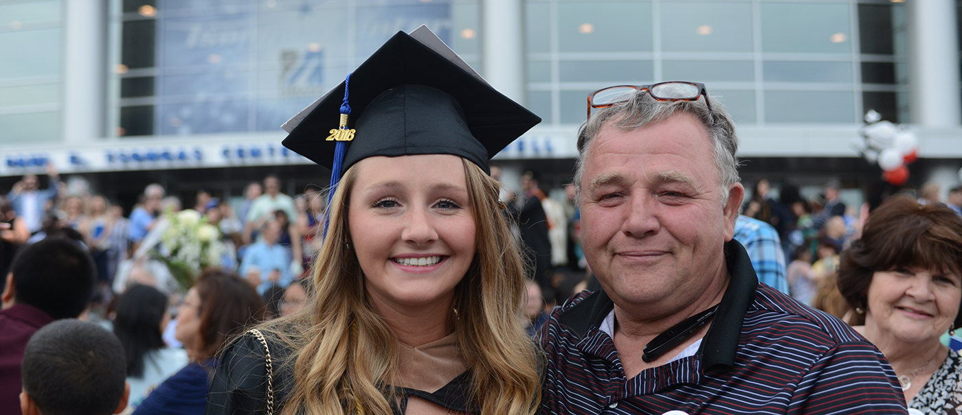 Dad and daughter who is a graduate at commencement