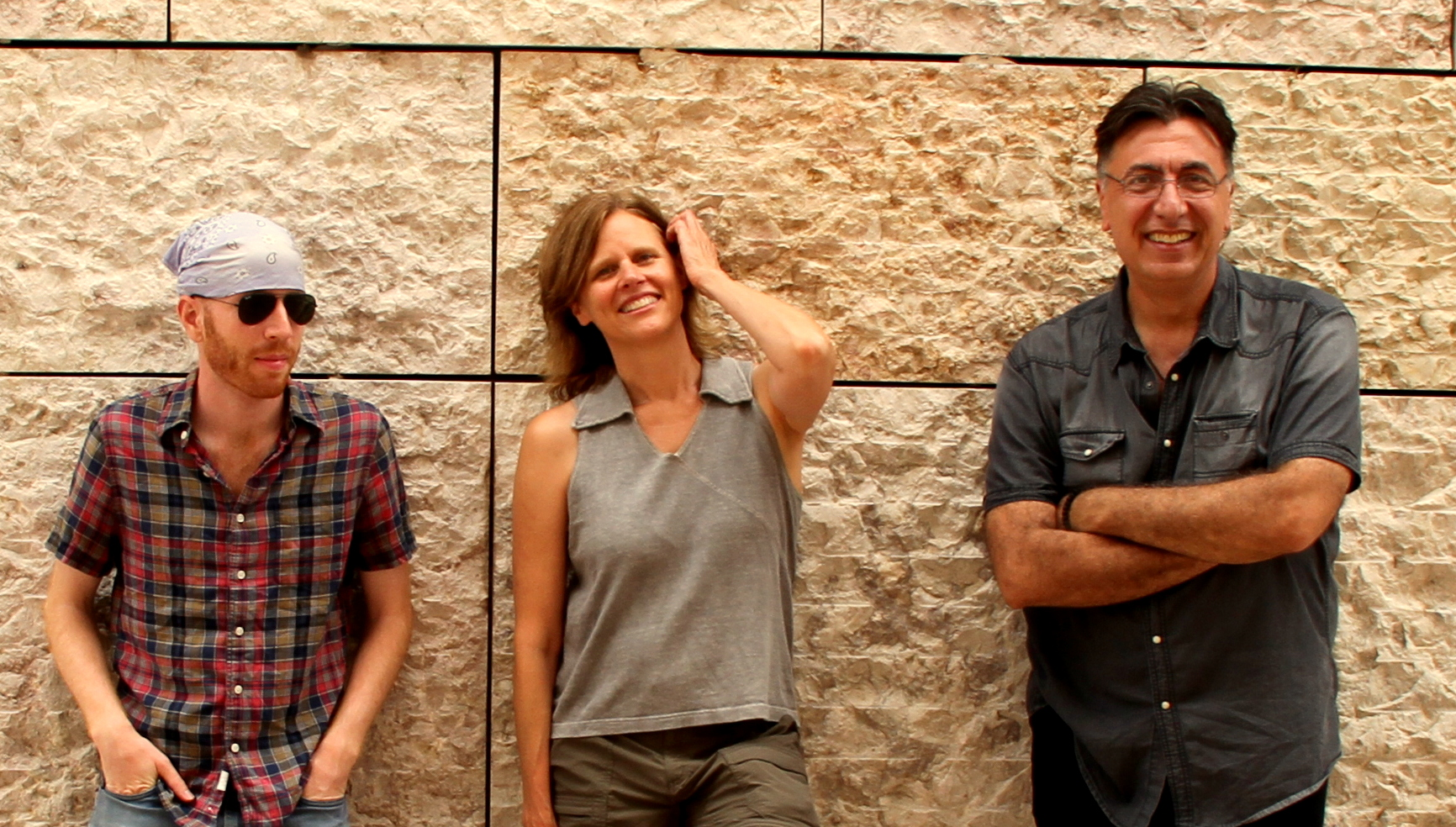Group photo of musical group Blue Thread:  Yaniv Yacoby, strings Cristi Catt, soprano Nikola Radan, flutes standing side by side against a wall.