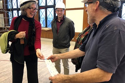Pocobene shows duct taped that was used to strip off the covering paint to Assoc. Prof. Marie Frank and university planner Adam Baacke.