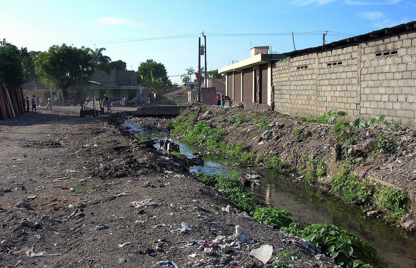 Poor sanitation in the area of Dlo Gervier, Cap-Haitien, Haiti : solid waste on the ground, drainage channel blocked, plastic bags containing excreta, road damaged by runoff water.