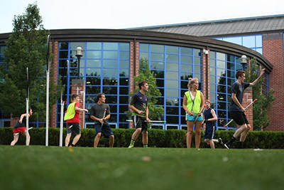 Club quidditch team players practice outside the Rec Center