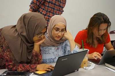 Sophomore Sarah Kamal assists incoming first-year engineering student Salwa Alhawi at UMass Lowell's RAMP camp, while Junyuan Hu works on a computing problem
