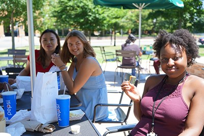 Yrvanie Joseph, right, enjoys the sun during lunch with Junyuan Hu and Katherine Vail, center