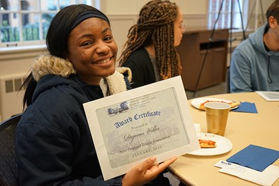 Psychology major and River Hawk Scholar Dejonai Willis displays her scholarship certificate from the Independent Association of University Alumni at Lowell
