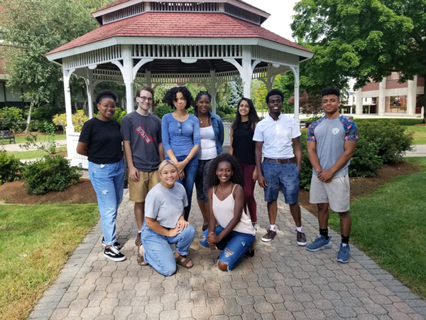 A group of River Hawk Scholars Academy Peer & Team leaders pose outside in front of the gazebo on South Campus