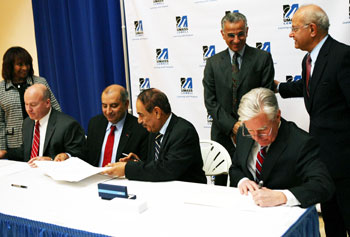 Shown signing the agreement are, from left, Stephen Murphy, vice president of contracts for Raytheon Integrated Defense Systems; Sanjay Kapoor, Raytheon vice president of Integrated Air and Missile Defense; GUST President Shuaib Shuaib; and UMass Lowell Chancellor Marty Meehan. Looking on are Marcellette Williams, UMass System senior vice president for academic and student affairs and international relations; Abdul-Rahman S. Al-Muhailan, chairman of GUST's board of trustees; and UMass Lowell Provost Ahmed Abdelal.
