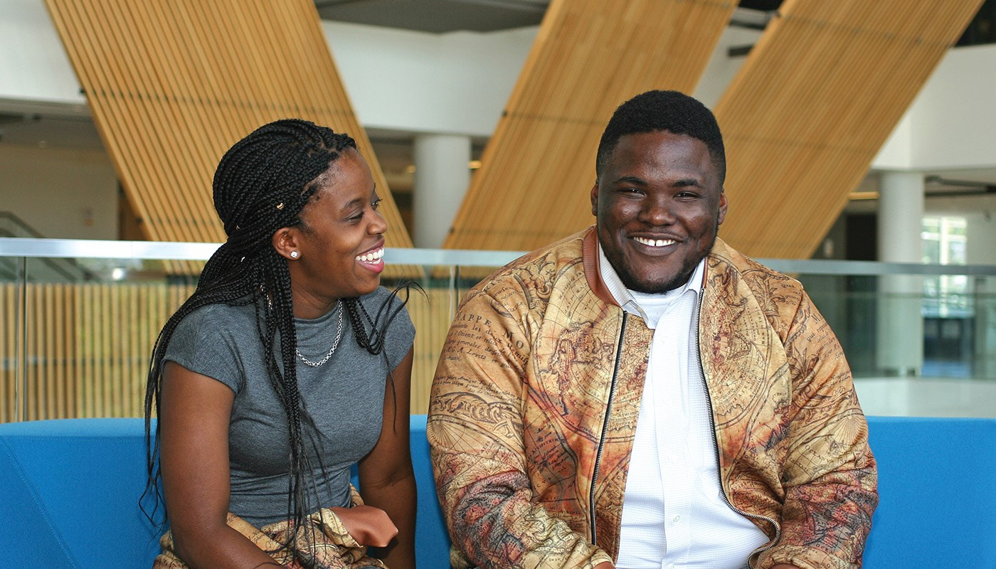 Electrical engineering alumnus and clothing designer Richard Asirifi laughing with friend at University Crossing