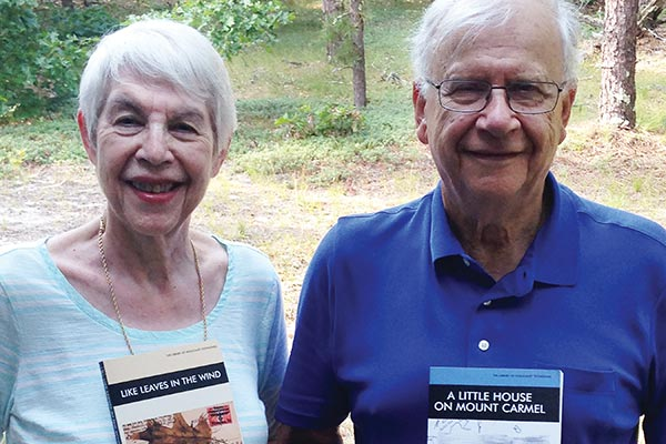 Emeriti chemistry professors Rita and Alexandre Blumstein with the memoirs they wrote about their families' experiences during World War II.