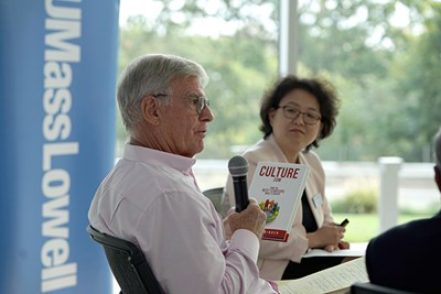 Robert Stringer holds a copy of his book while Yi Yang looks on