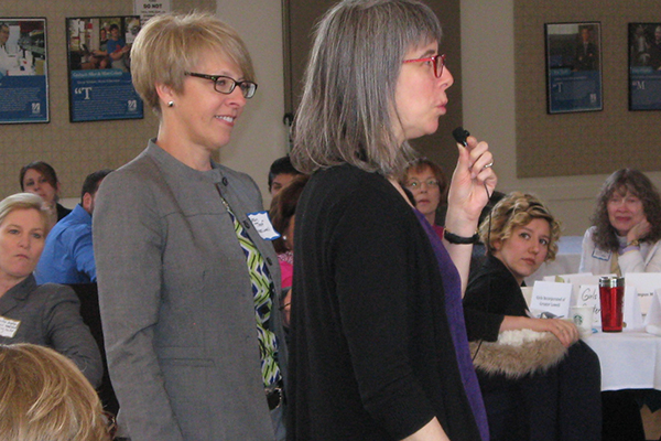Robin Toof passes the microphone to Lowell math teacher Nili Pearlmutter at the 2016 Community Connections Breakfast.