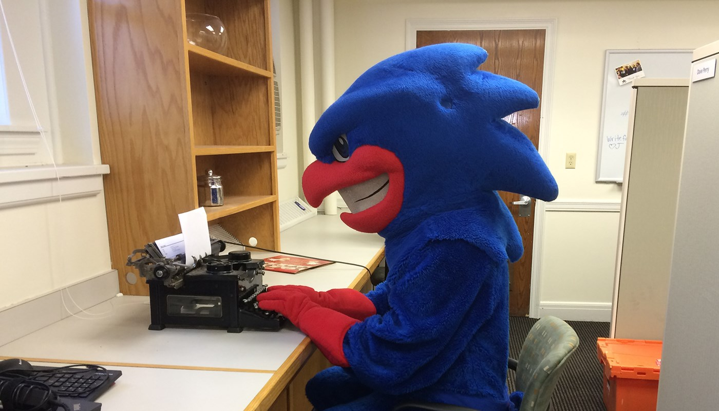 Rowdy the River Hawk (mascot) sitting typing at a typewriter.