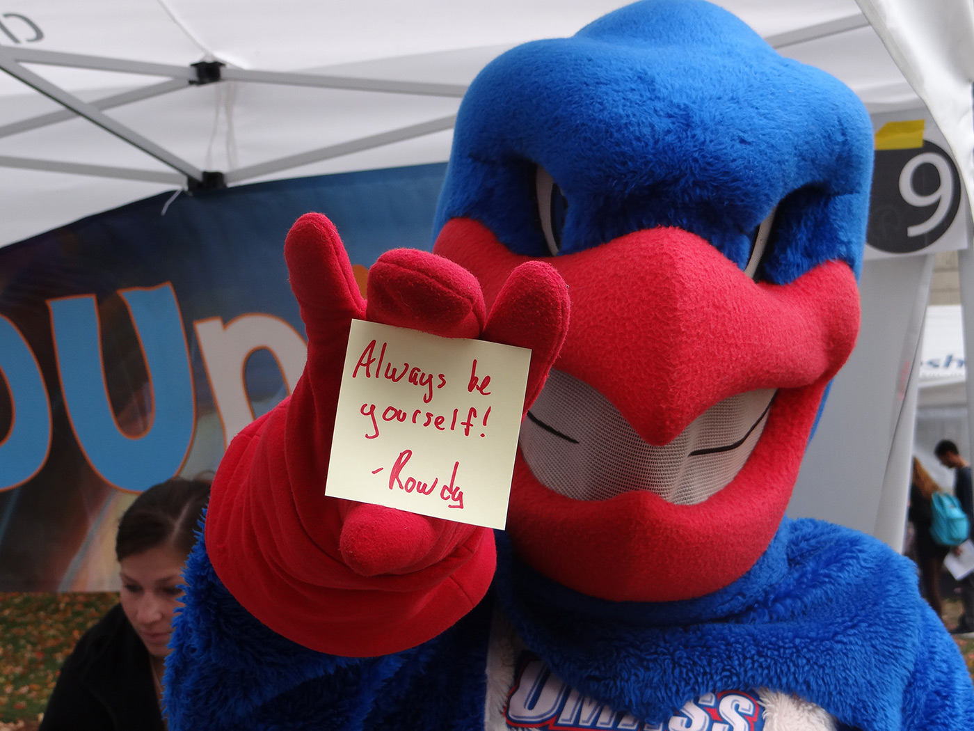 "UMass Lowell mascot, Rowdy the River Hawk holding out a post-it note that say ""Always be yourself!"""