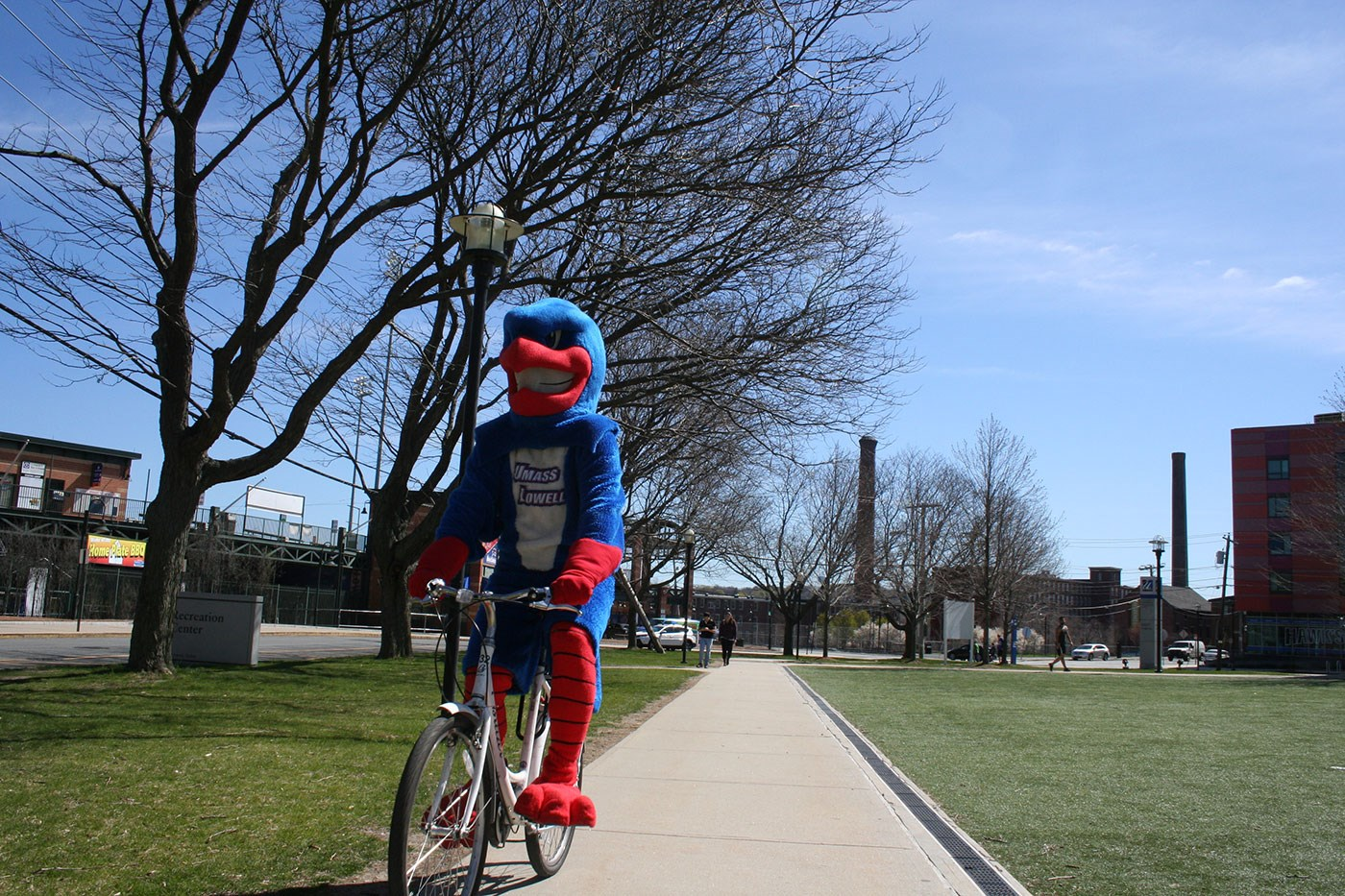Umass Lowell's mascot Rowdy, riding a bike.