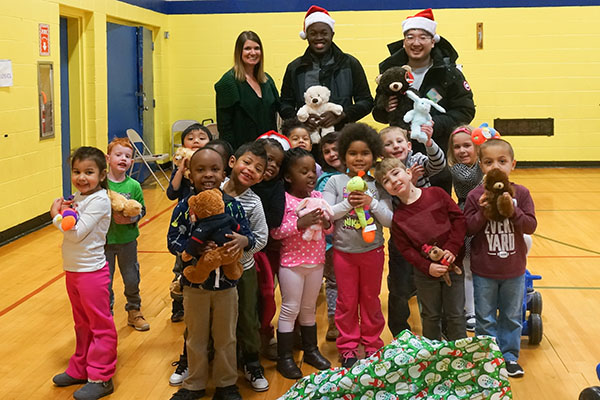 "Student Alumni Ambassadors Ralph Saint Louis '18 (at rear, center) and Qin ""Sal"" Li distributing stuffed animals to children at the Lowell YMCA Preschool."