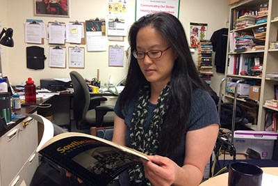 English Prof. Sue Kim looks through Higgins & Ross book of photos of Cambodian refugees in Lowell