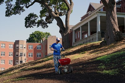 A grounds employee spreads seed behind the Allen House on South Campus