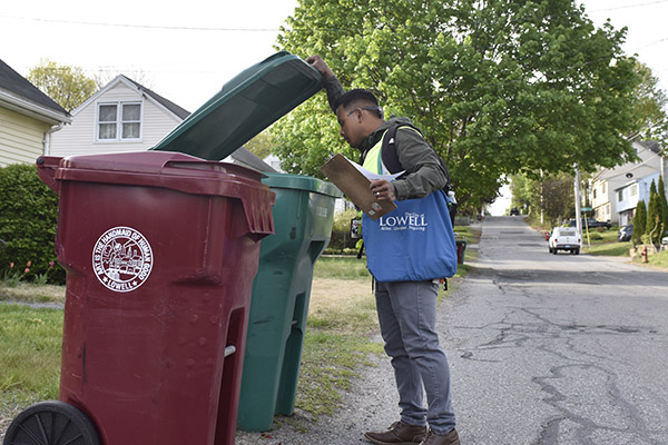 Bora Chhun checks a recycling bin for contamination.
