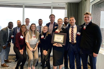 Business students pose with their winning certificate at the UMass Club