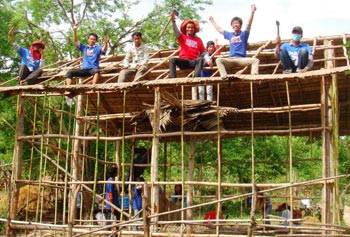 Volunteers celebrate completing the framework, as they build new houses for poor families in rural Cambodia. Directed by student Tola N. Sok, Project Save One Khmer built six houses in nine days.
