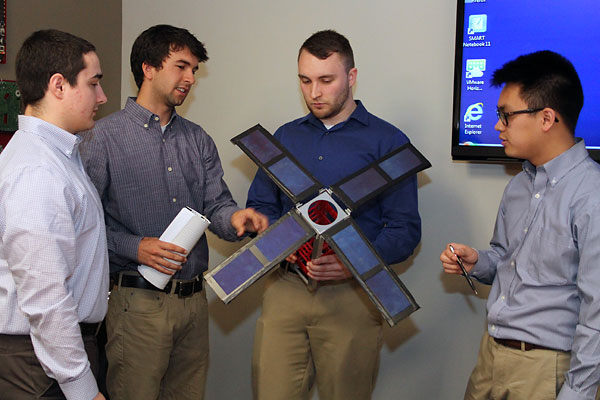 Team members with a satellite model