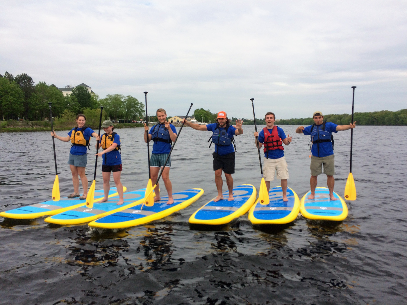 Six people on paddleboards with hands in the air