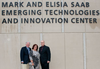 Chancellor Marty Meehan, left, stands with Elisia and Mark Saab below the newly unveiled name of the university's $80 million academic building.