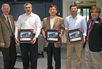 Chancellor Marty Meehan, far left, and Engineering Dean John Ting, far right, present framed photos of the 4D Home built by Team Massachusetts to, from left, Boris Serebrennikov, Oh-Hun Kwon and Mithun Kamath of Saint-Gobain.