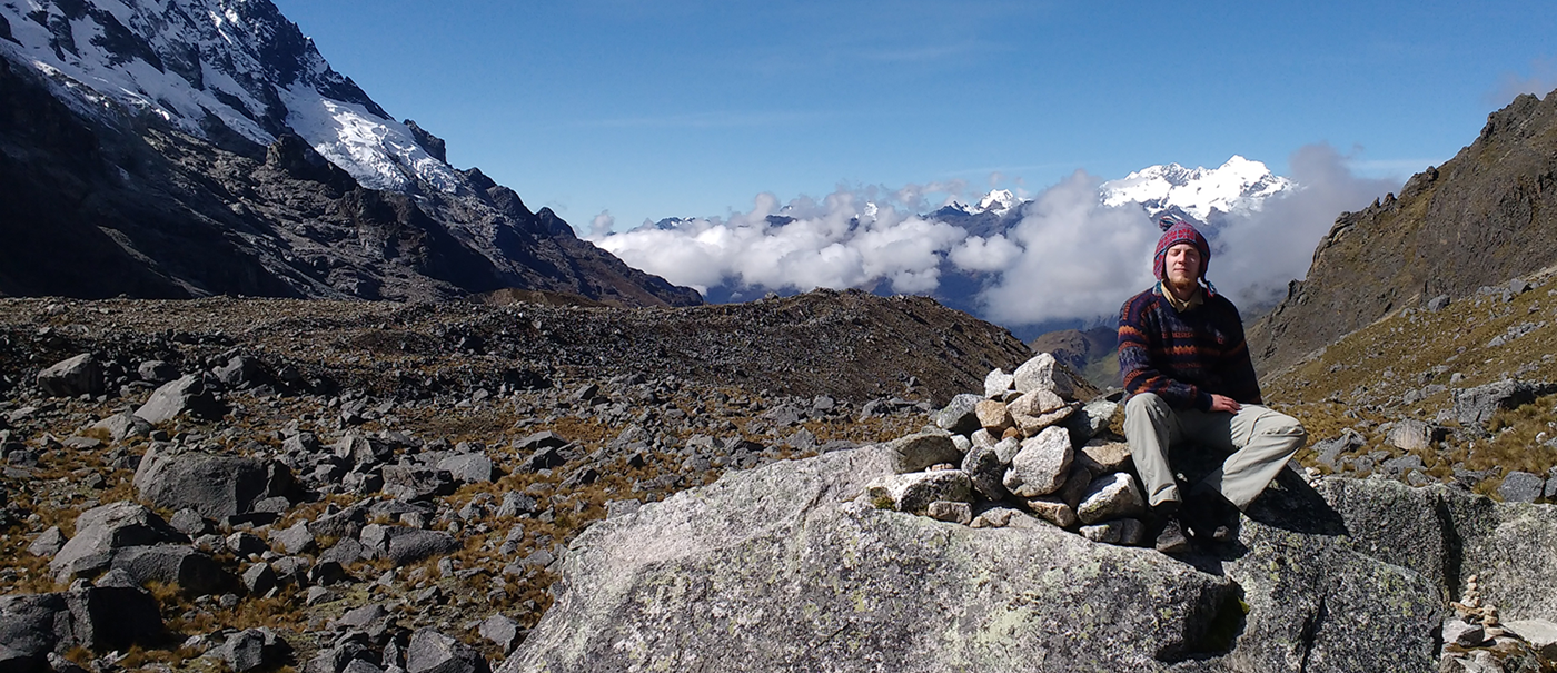 Sean Cloran sitting on rock formation in the Peruvian Andes