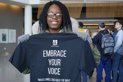 First-year UML student Claudiegh Decoline of Kappa Delta Phi holds up a Take Back the Night t-shirt