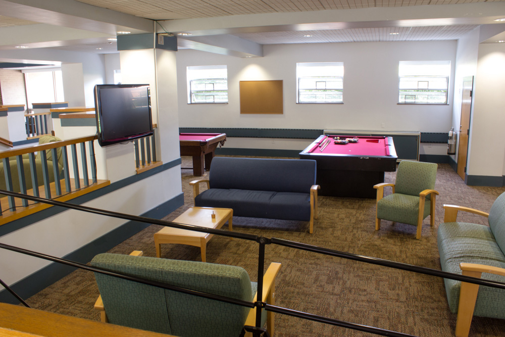 Sheehy Hall lounge area and pool tables. All the rooms are suite-style with a bathroom and a common area. Sheehy Hall is located on South Campus and has the best view of the Merrimack River!