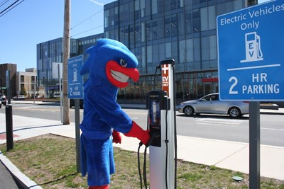 Rowdy the River Hawk using an electrical vehicle charging station on campus