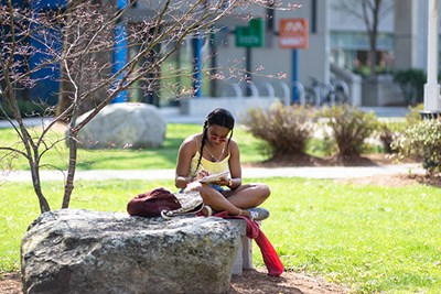 A student studies outside on South Campus