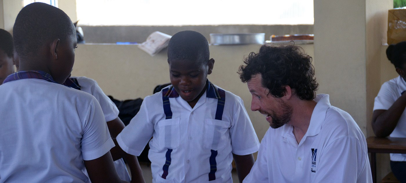 UMass Lowell Physics Lecturer teaching two young Haitian boys on a trip to Haiti in 2016.