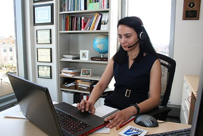 Faculty member Saira Latif uses a bluetooth headset to make a Skype call
