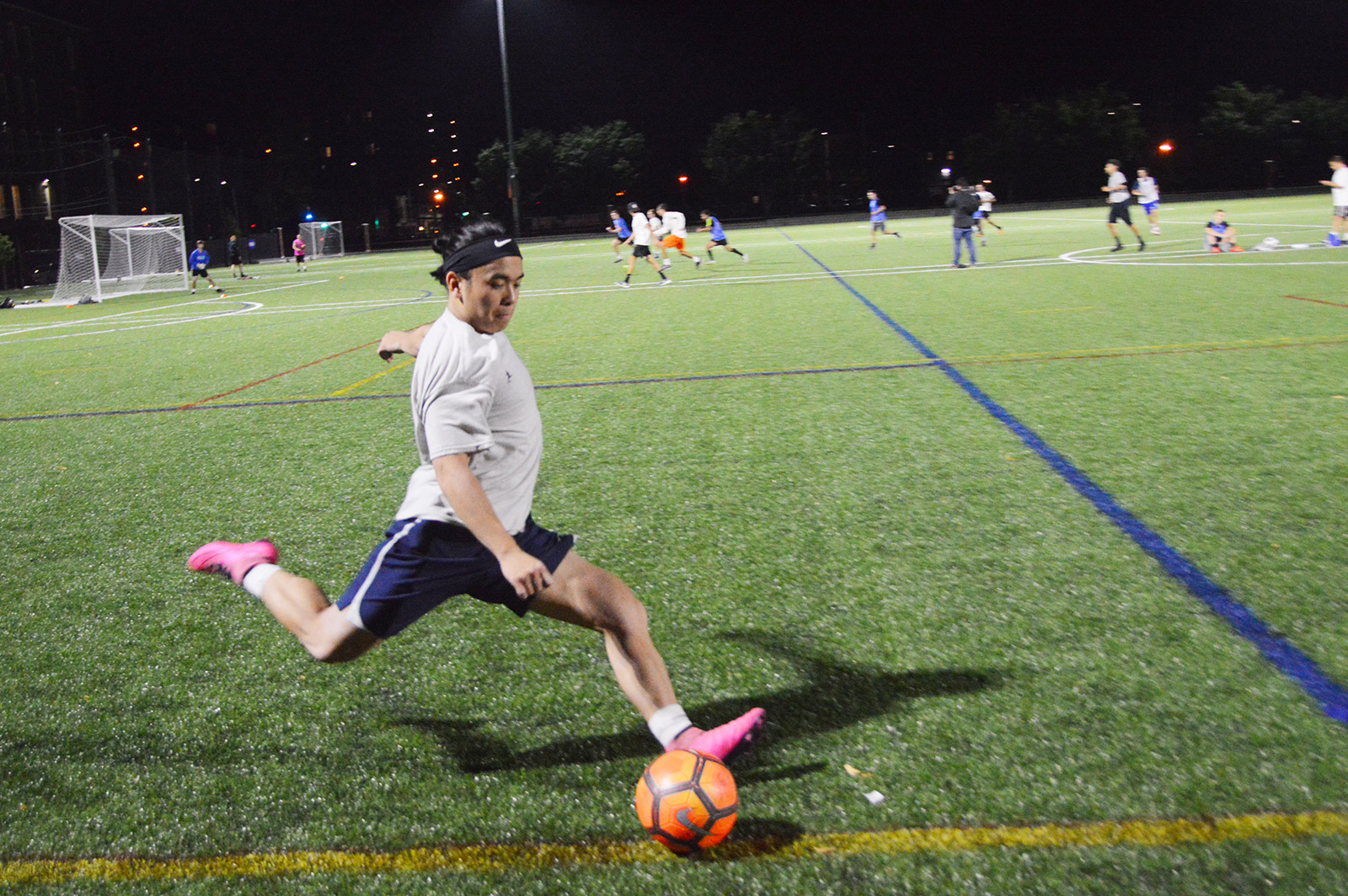 student playing soccer on campus rec complex turf field