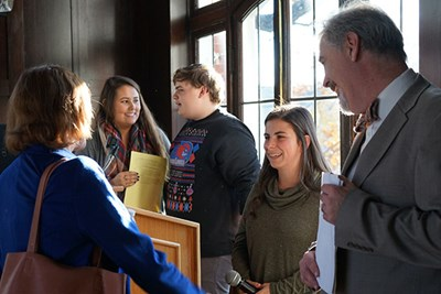 Vice Provost Julie Nash, left, and sociology lecturer Thomas Pineros-Shields, right, chat with students after their presentation on college debt