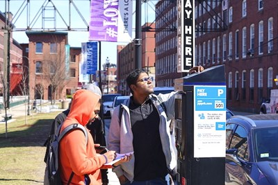 Students inspect a solar panel on a parking kiosk on Jackson Street