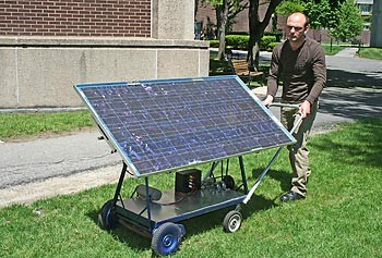 Electrical engineering undergraduate student Samuel Hamill demonstrates the operation of his prototype solar-powered push mower. The mower's solar panel moves to keep the panel facing the sun.