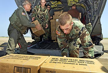 U.S. Army soldiers load boxes of Meals, Ready to Eat (MREs) onto a CH-47 Chinook helicopter.