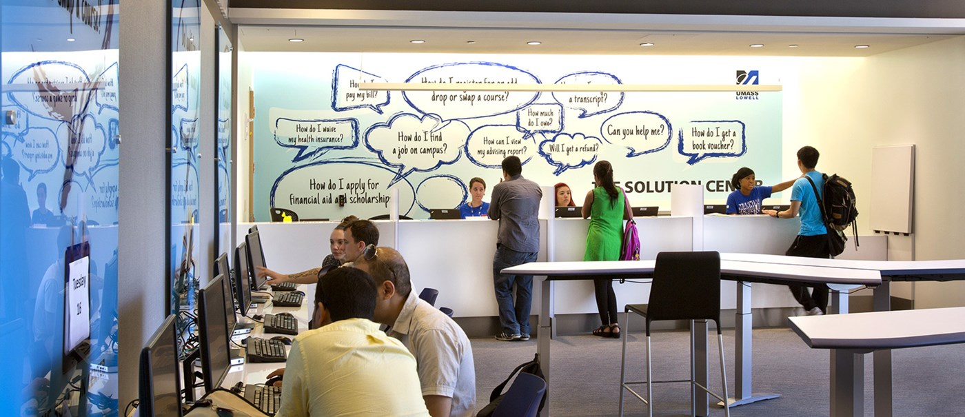 Exterior of Umass Lowell Solution Center, group of students getting assistance at desk and computers from Solution Center members.