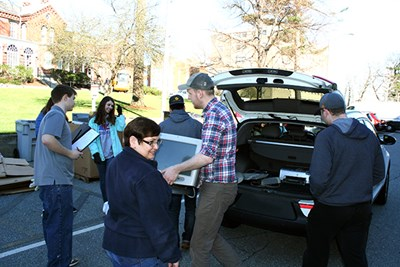 Students unload electronics from a car