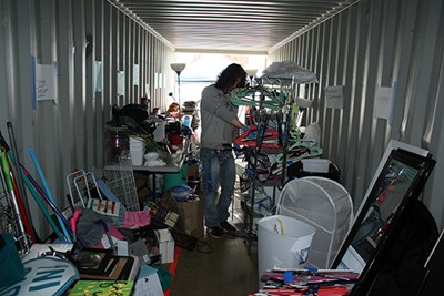 A student organizes donations in a shipping container