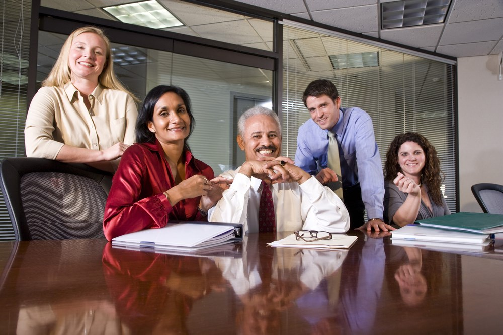 Stock image of people smiling around a table - Steering Committee Photo