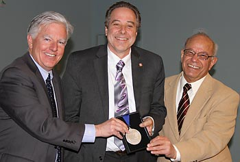 Prof. Stephen McCarthy, center, is presented with the Distinguished University Professor medallion by Chancellor Marty Meehan, left, and Provost Ahmed Abdelal.