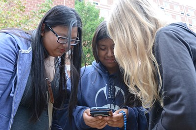 Students check out an app on a mobile device