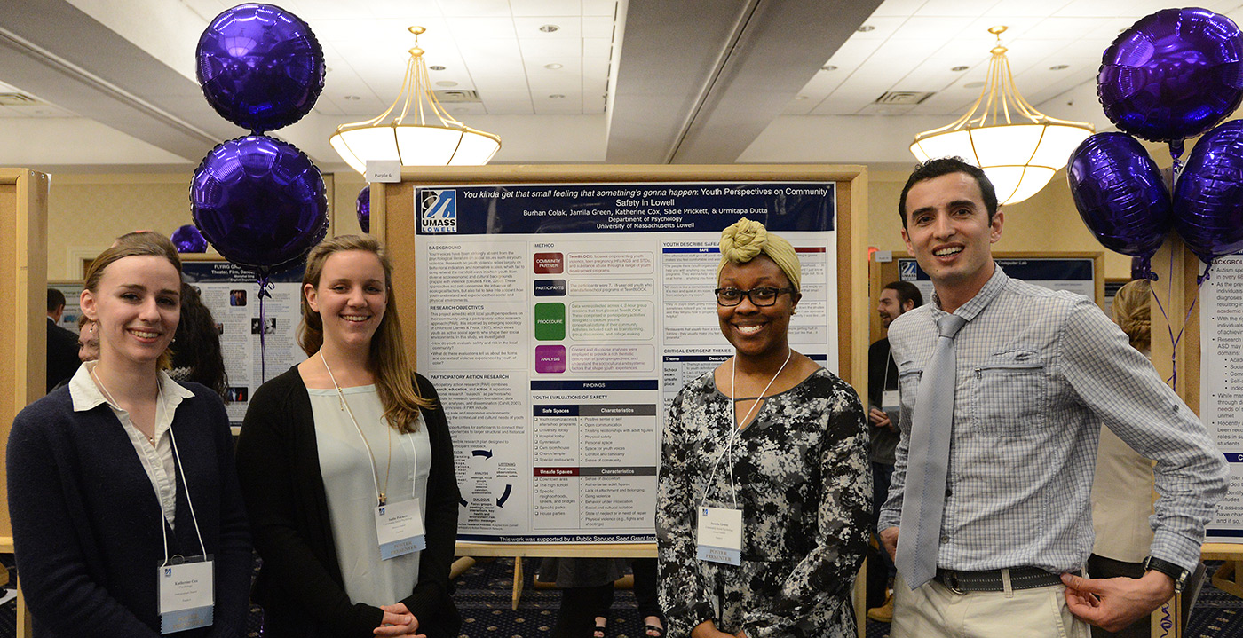 Three female and one male students pose for a group photo at the UMass Lowell Student Research Symposium