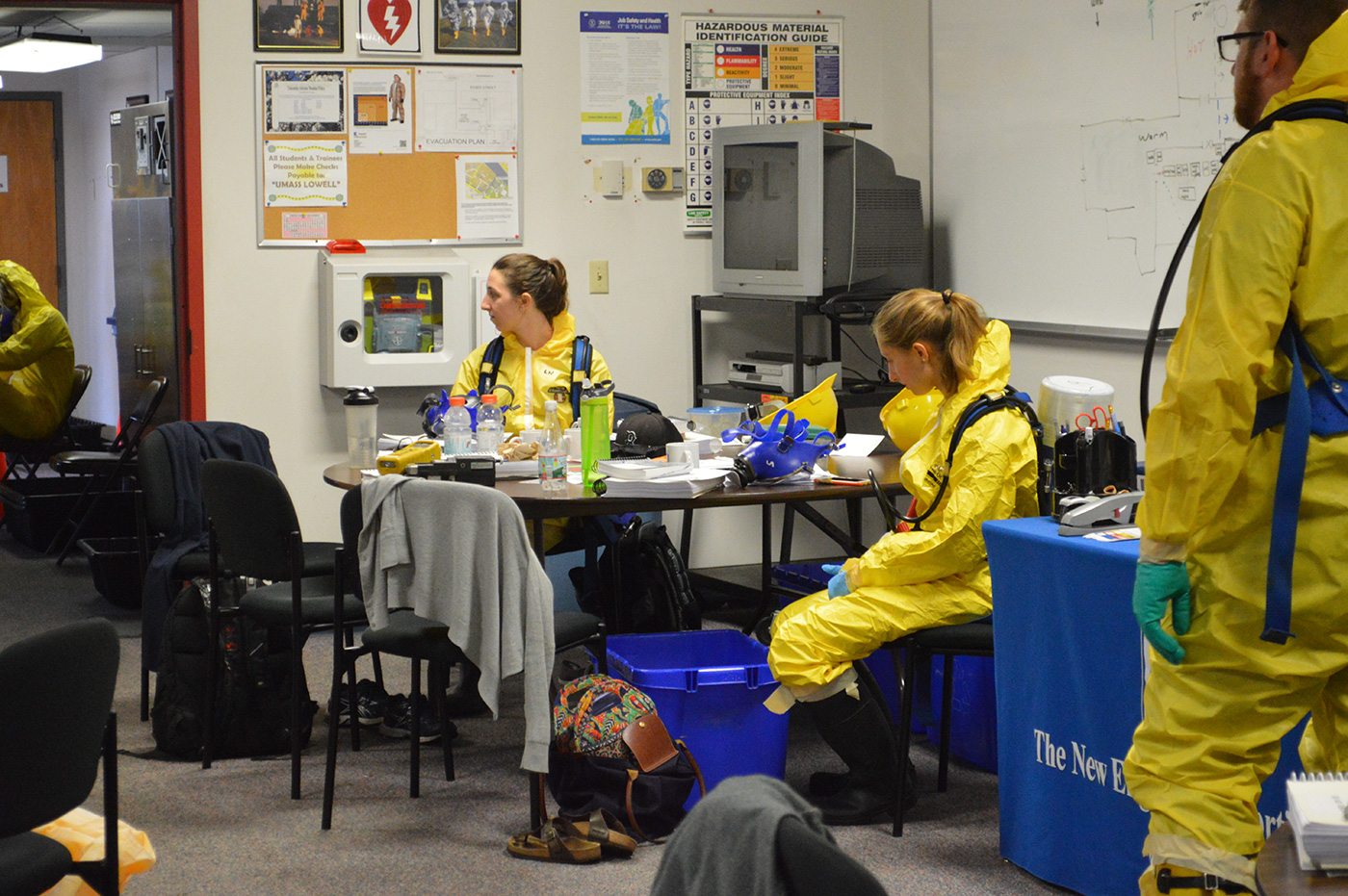 "Students in a 40-Hour basic hazardous waste health and safety course are sitting in the TNEC training room dressed in their Class ""B"" suits and oxygen tanks. They are awaiting instructions from the trainer."