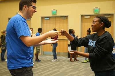 Students in UMass Lowell's new River Hawk Scholars Academy plan rock, paper, scissors at a welcome event.