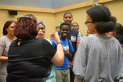 Amy Liss in Student Activities leads students in a team-building activity at a welcome event for the River Hawk Scholars Academy at UMass Lowell