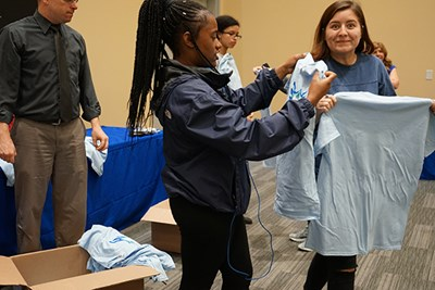 Members of UMass Lowell's new River Hawk Scholars Academy check out their official t-shirts.